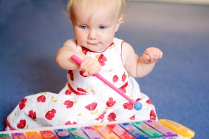 baby girl playing toy xylophone