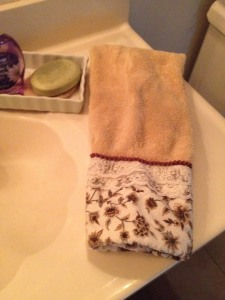 a folded hand towel, near a clean sink