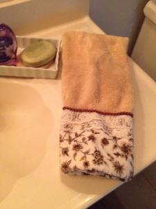 a folded hand towel, near a clean sink